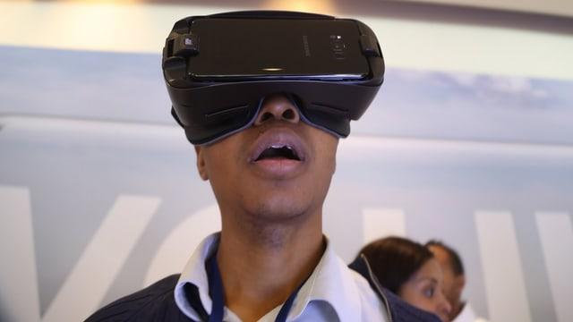 Ein Mann mit einer Samsung-Gear-VR-Brille auf dem Kopf.