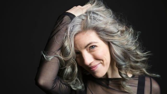 Eine Frau lächelt in die Kamera, die Hand in ihren grauen Haaren.