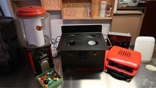 Ein Kaugummispender, ein Spielzeugholzherd, ein roter Kofferplattenspieler
