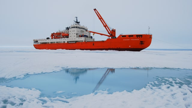 Rot-weisses Schiff, im Vordergrund Eis und Wassertümpel