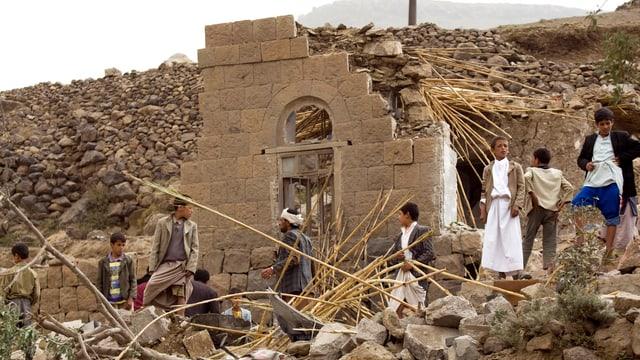 Bewohner vor einem komplett zerstörten Gebäude.
