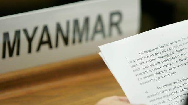 Platz Myanmars bei der UNO mit einem Schild. Jemand hält ein Ballt Papiert in der Hand.