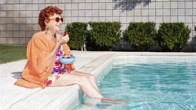 Eine ältere Frau sitzt mit einem Drink am Pool.