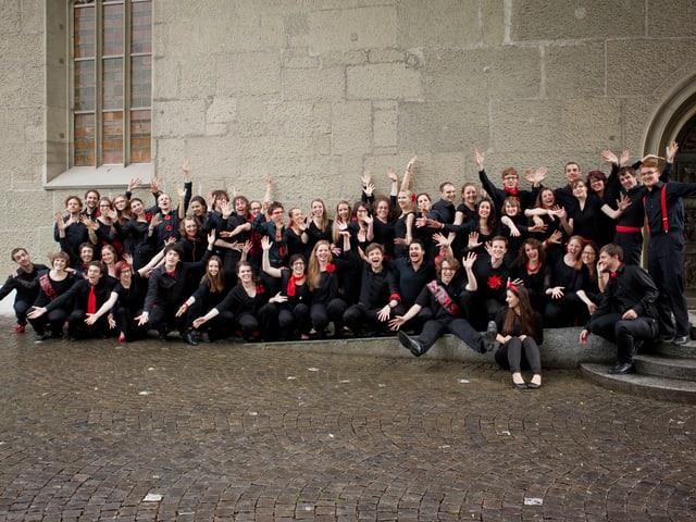 Die Sängerinnen und Sänger tragen schwarze Kleider mit roten Accessoires und posieren kniend für Gruppenfoto.