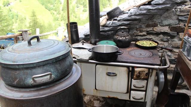 Ein Holzherd vor der Hütte mit ein paar schwarzgebrannten Pfannen.