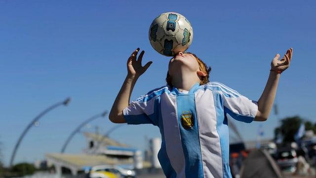 Ein junger Argentinien-Fan spielt einen Kopfball.