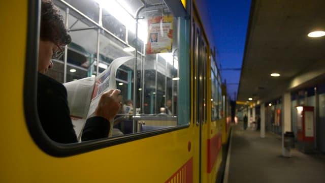 Blick durch Tramfenster auf eine Frau, die in der Zeitung liest.