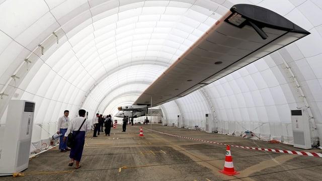 Ein weisses, langes Zelt als Hangar für das Solarflugzeug mit seinen langen Flügeln.