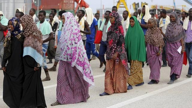 Frauen mit bunten Kopftüchern gehen in einer Reihe in einem Hafen.