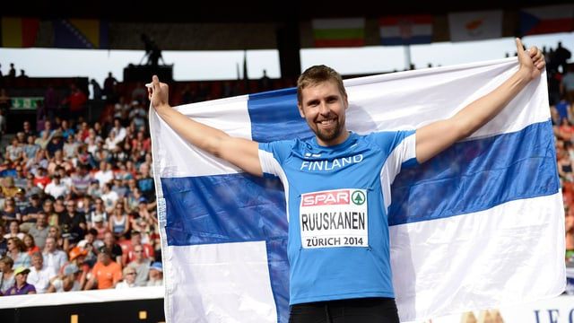 Antti Ruuskanen posiert mit der finnischen Fahne.