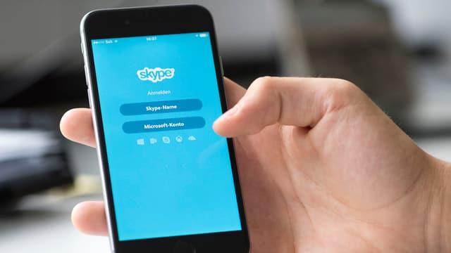 Eine Hand hält ein Handy, auf dem die Icons der WhatsApp und der Skype-App zu sehen sind.