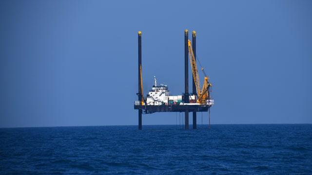 Ein Schiff ist mit drei grossen Pfeilern über dem Meeresspiegel aufgehängt.
