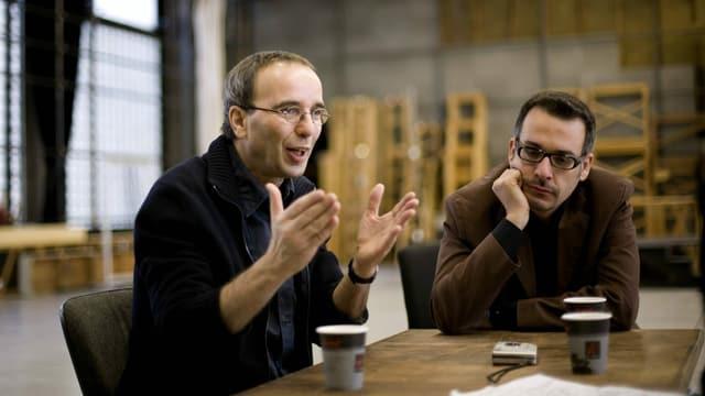 Mann mit kurzen Haaren und schlichter Brille spricht und gestikuliert akzentuiert mit beiden Händen. Neben ihm am Tisch sitzt ein weiterer Mann mit Hornbrille und hört aufmerksam zu.