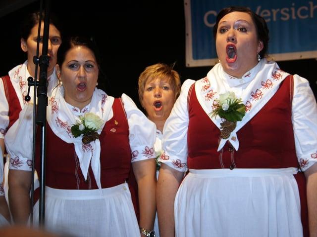 Vier Jodlerinnen mit weissen Blusen unter roten Röcken mit weissen Schürzen.
