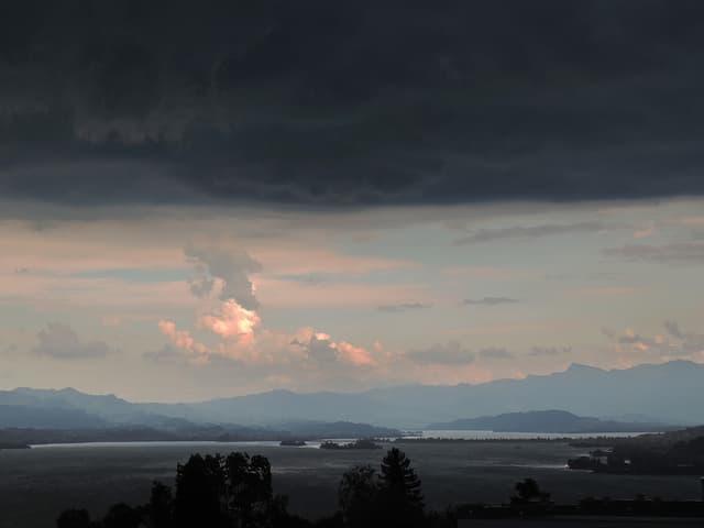 Düstere Wolken ziehen auf, unten der See stark bewegt.