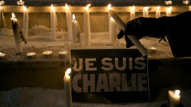 Kerzen und Je suis Charlie-Plakat.