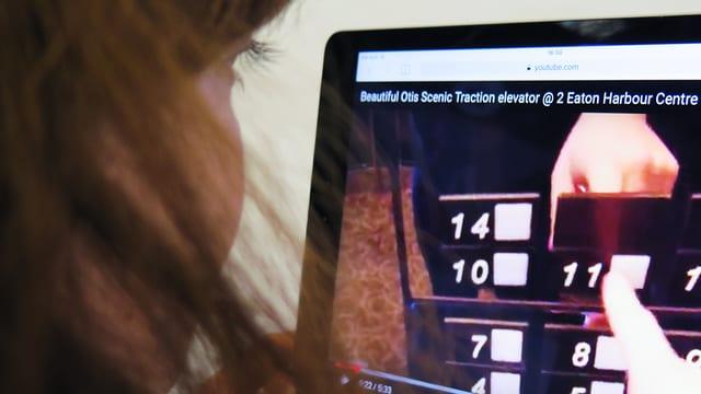 Eine Frau sieht sich ein Fahrstuhlvideo auf Youtube an.