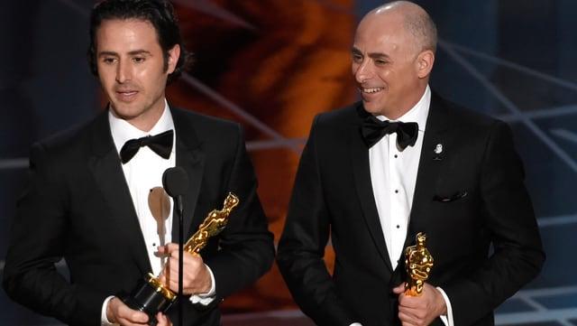 Zwei Männer mit Anzug und Oscar-Statue sprechen in ein Mikrofon.