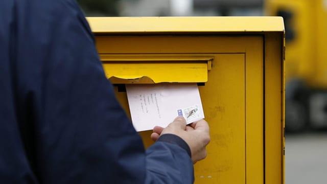 Ein Mann steckt einen frankierten Umschlag in einen Briefkasten