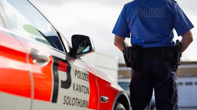 Ein Polizist steht neben einem Polizeiauto mit der Aufschrift Polizei Kanton Solothurn.