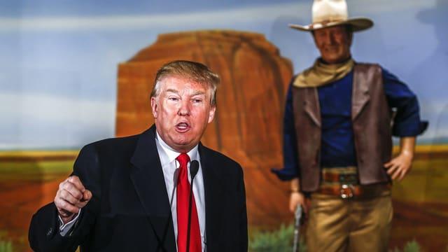 Ein Mann spricht vor einer John-Wayne-Statue.