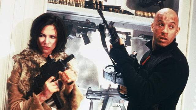 Eine Frau im Pelzmantel und ein glatzköpfiger Mann halten je eine Schusswaffe in der Hand.