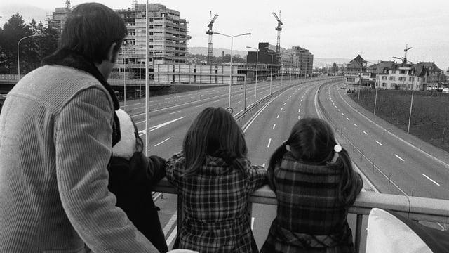 Mann mit Mädchen auf einer Brücke über einer leeren Schnellstrasse