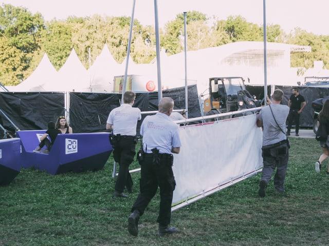 Mitarbeiter tragen Material über das Gelände