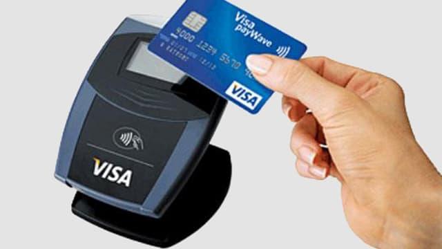 Eine Frau hält eine Visa-Karte an ein Lesegerät.