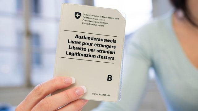 Angestellte einer Migrationsbehörde hält Ausländerausweis B in der Hand
