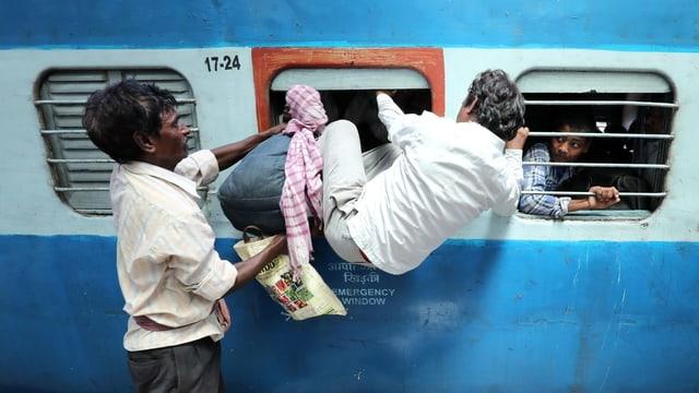 Mann steigt durch Fenster in einen Zug ein