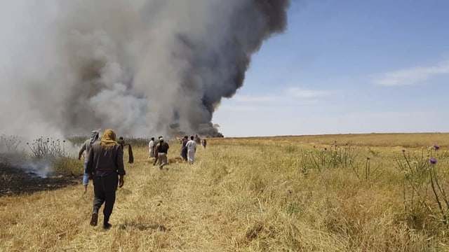 Menschen versuchen am 28. Mai 2019 in Jaabar in der Provinz Rakka ein Feuer zu löschen.