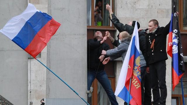 Demonstranten hissen eine russische Fahne bei einem Regierungsgebäude.