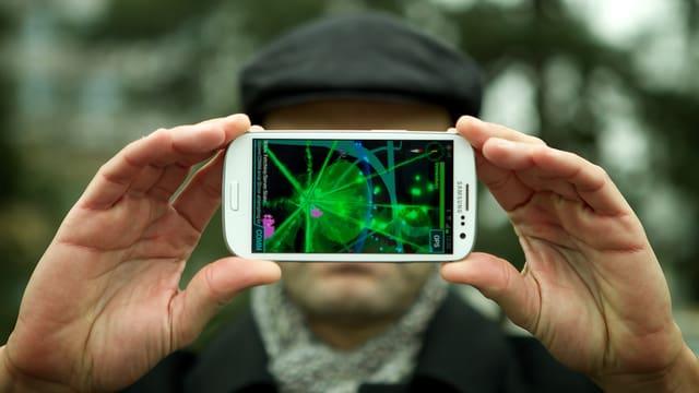 Reto Widmer von der SRF Digitalredaktion hält sein Smartphone in der Hand, auf dem ein Portal von Google Ingress beim Zürcher Bucheggplatz grün leuchtet.