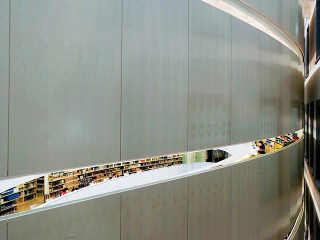 Blick durch eine Öffnung in der Mauer in die Bibliothek, wo Bücherregale und ein langgeschwunger Tisch zu sehen sind.