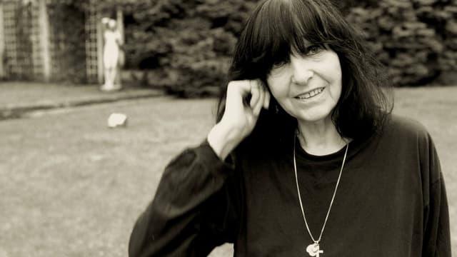Friederike Mayröcker, gekleidet in schwarz und Kette mit Kreuz, draussen vor einem Haus stehend, sich ans Ohr fassend.