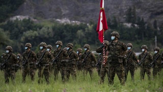 Soldaten (mit Gesichtsmaske) stehen in einem Feld, einer hält eine Schweizer Fahne.