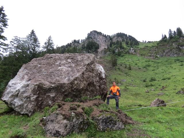 Ein Mann mit orangem Oberteil steht neben einem fast haushohen Felsblock.