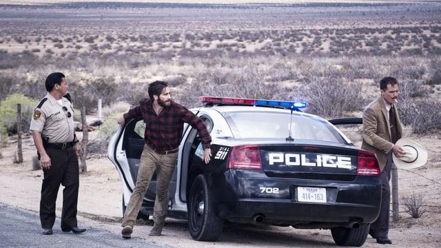 Ein Polizist und zwei Männer in Zivil stehen neben einem Polizeiauto in der Wüste.