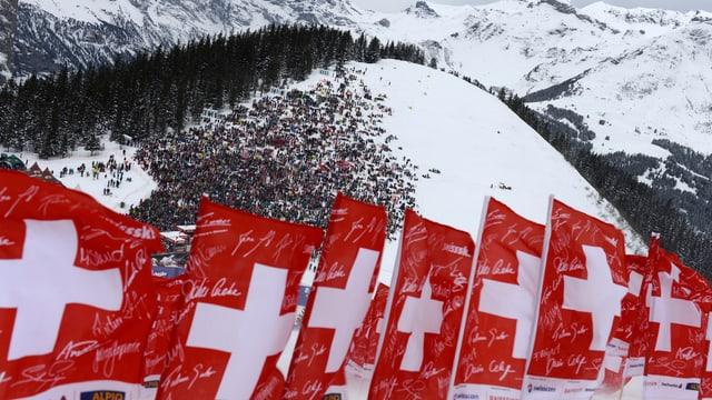 Schweizer Fahnen im Schnee vor der Zuschauerkulisse.