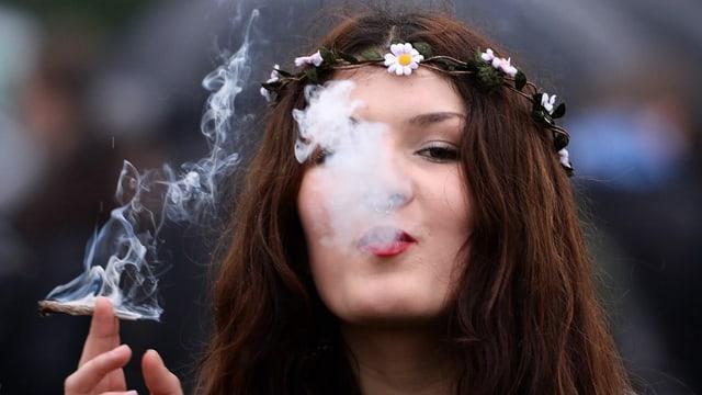 Eine Frau bläst Cannabis-Rauch aus