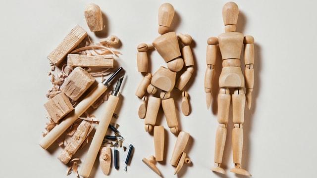 Marionetten, die nebeneinander liegen. Die eine ist ganz, die andern sind teilweise auseinandergebaut.