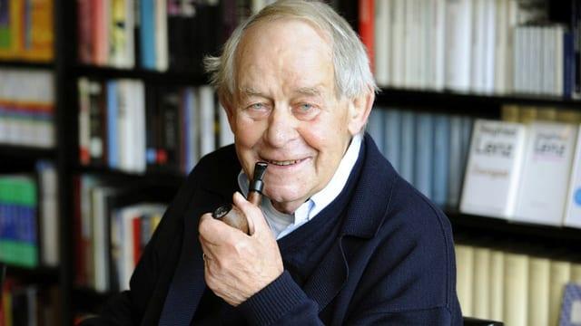 Der Schriftsteller Siegfried Lenz Pfeife rauchend vor einem Büchergestell.