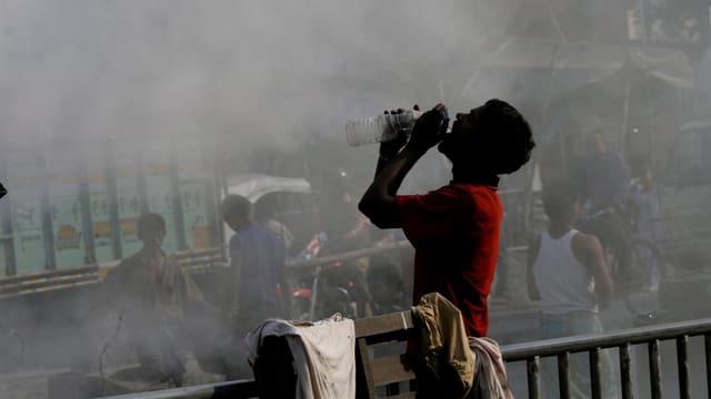 Ein Mann trinkt Wasser in Kalkutta, Rauch steigt hinter ihm auf