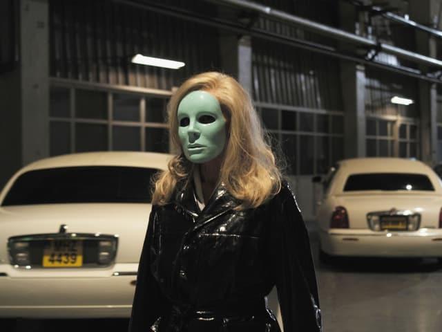 Eine Frau mit einer grünen Maske schreitet durch eine Tiefgarage mit Limousinen.