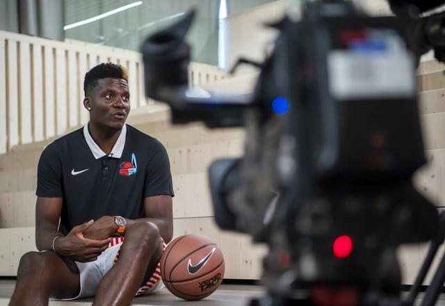 Clint Capela sitzt neben einem Basketball, eine Filmkamera nimmt ihn dabei auf