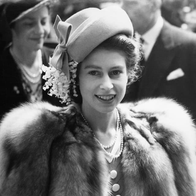 Queen Elizabeth, lura anc princessa, cun 21 onns a Londra. Gia lura segira da ses stil cun chadaina da perlas e chapè elegant.