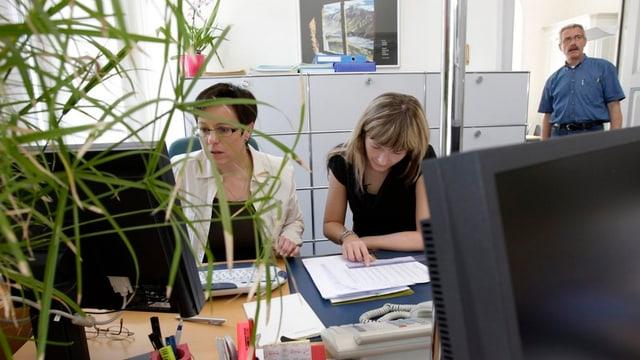 Zwei Frauen aus der Glarner Verwaltung sitzen an einem Tisch und studieren Akten.