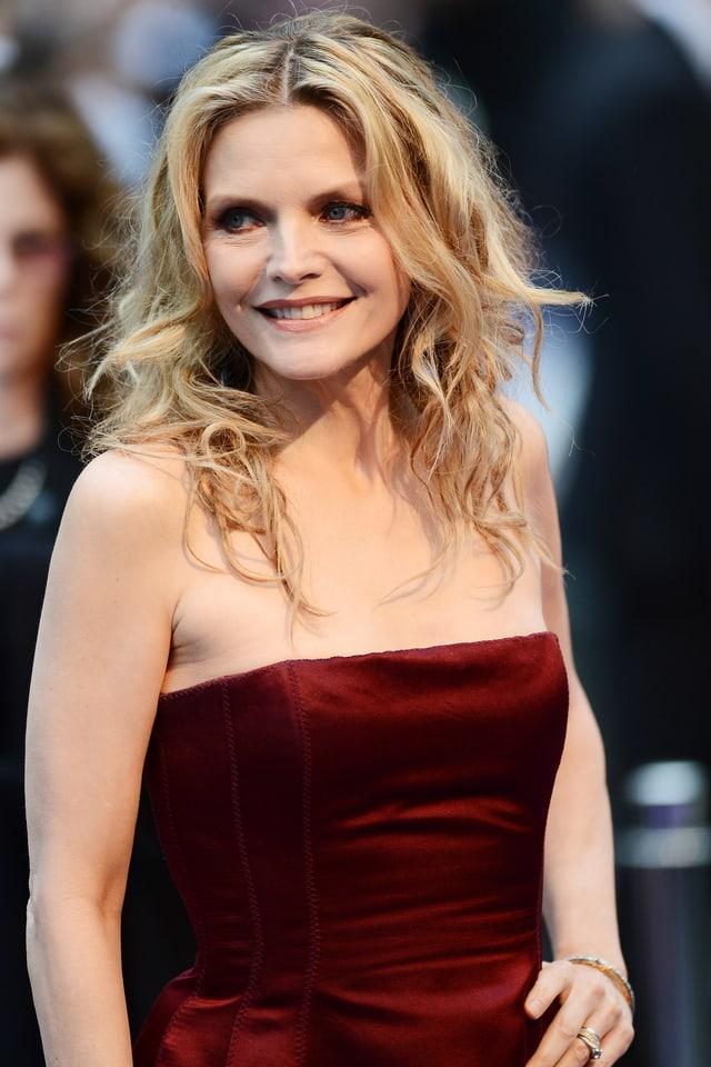 Frau mit blonden Locken in rotem Kleid.