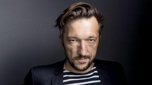 Ein Portrait von Autor Lukas Bärfuss, im gestreiften T-Shirt mit schwarzem Anzug.